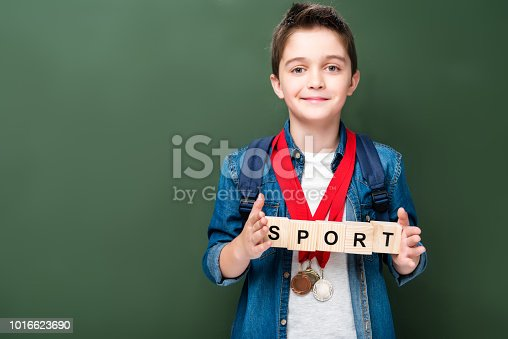 1016623732istockphoto schoolboy with medals holding wooden cubes with word sport near blackboard 1016623690