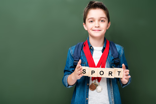 1016623732 istock photo schoolboy with medals holding wooden cubes with word sport near blackboard 1016623690