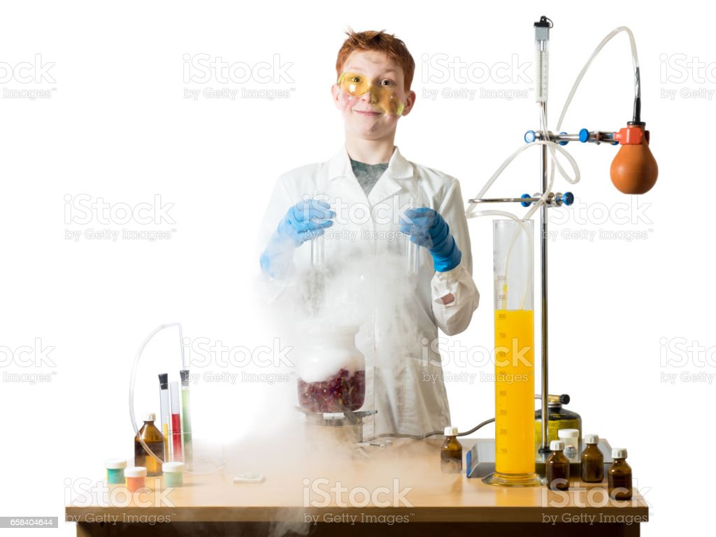 Schoolboy with move out on his nose glasses stands in a white robe beside chemical table and holds in hands of the flask in the background laboratory equipment stock photo