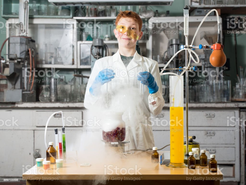 Schoolboy with move out on his nose glasses stands in a white robe beside chemical table and holds in hands of the flask on a background of chemical laboratory with table and chemical equipment stock photo