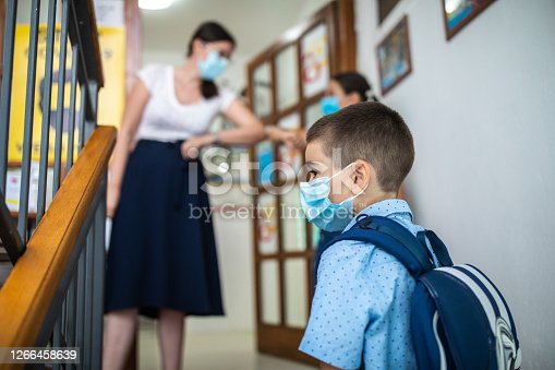 Teacher greeting school children with elbow bump before they enter school, they are wearing protective face masks for protection against virus during covid-19 pandemic