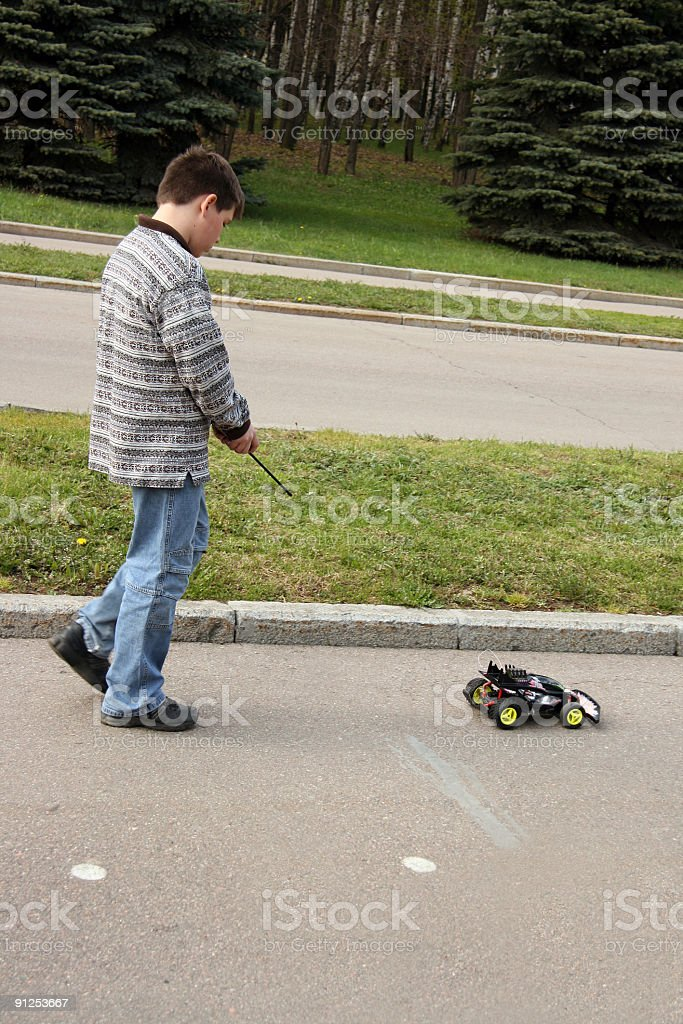 schoolboy with  toy car in park stock photo