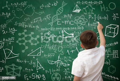 istock schoolboy writing math formula on blackboard 506854680