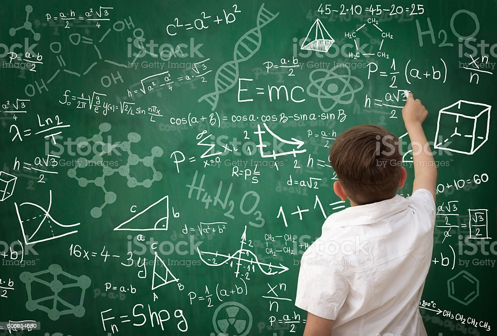 schoolboy writing math formula on blackboard stock photo