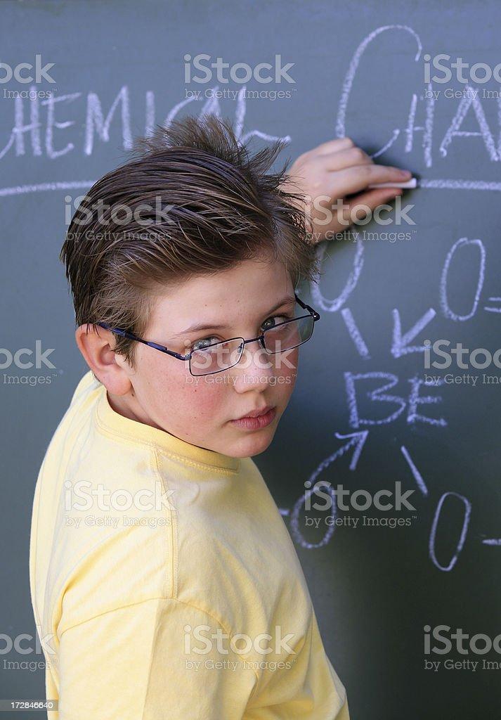 Schoolboy writing on a blackboard royalty-free stock photo