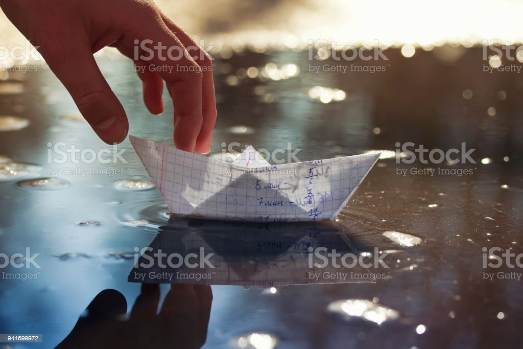 childrens hand of the schoolboy launches a small paper boat made of a...