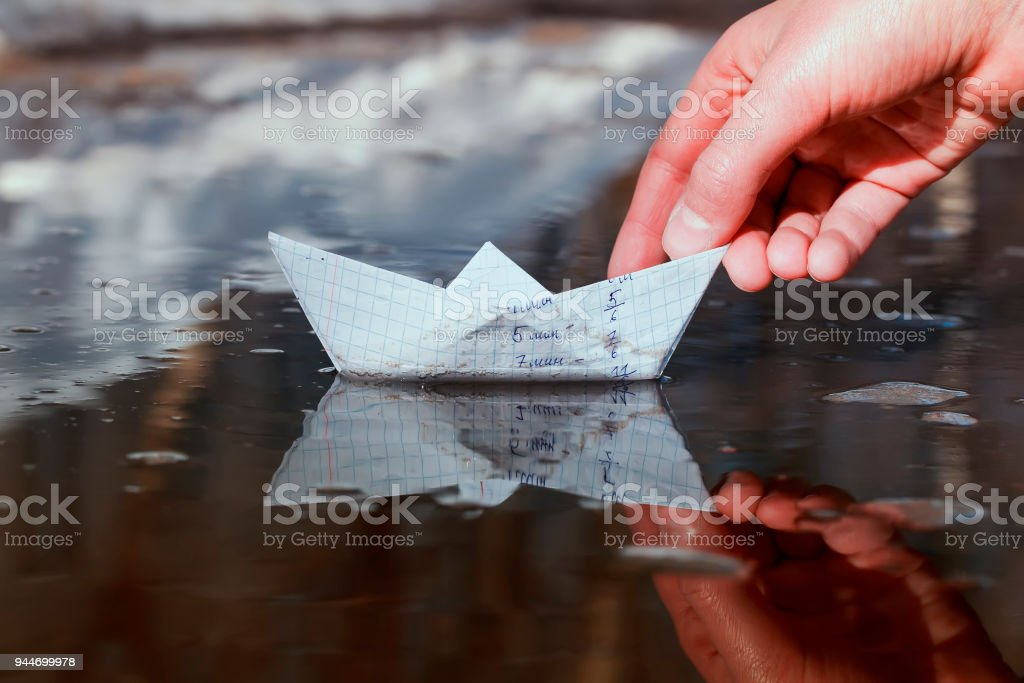 the schoolboy\'s hand launches a small paper boat made of a school...