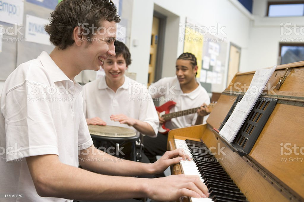 Schoolboys playing musical instruments in music class stock photo