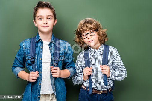 1016623732istockphoto schoolboys with backpacks looking at camera near blackboard 1016623712