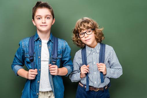1016623732 istock photo schoolboys with backpacks looking at camera near blackboard 1016623712