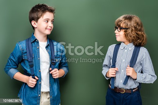 1016623732istockphoto schoolboys with backpacks looking at each other near blackboard 1016623674