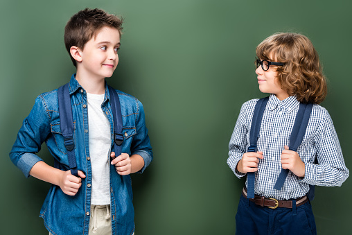 1016623732 istock photo schoolboys with backpacks looking at each other near blackboard 1016623674
