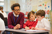 Two schoolboys work through a textbook with their teacher in elementary class. This is a school in Hexham, Northumberland in north eastern England.