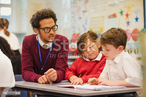 istock Schoolboys Work with their Teacher in Elementary Class 1007227306