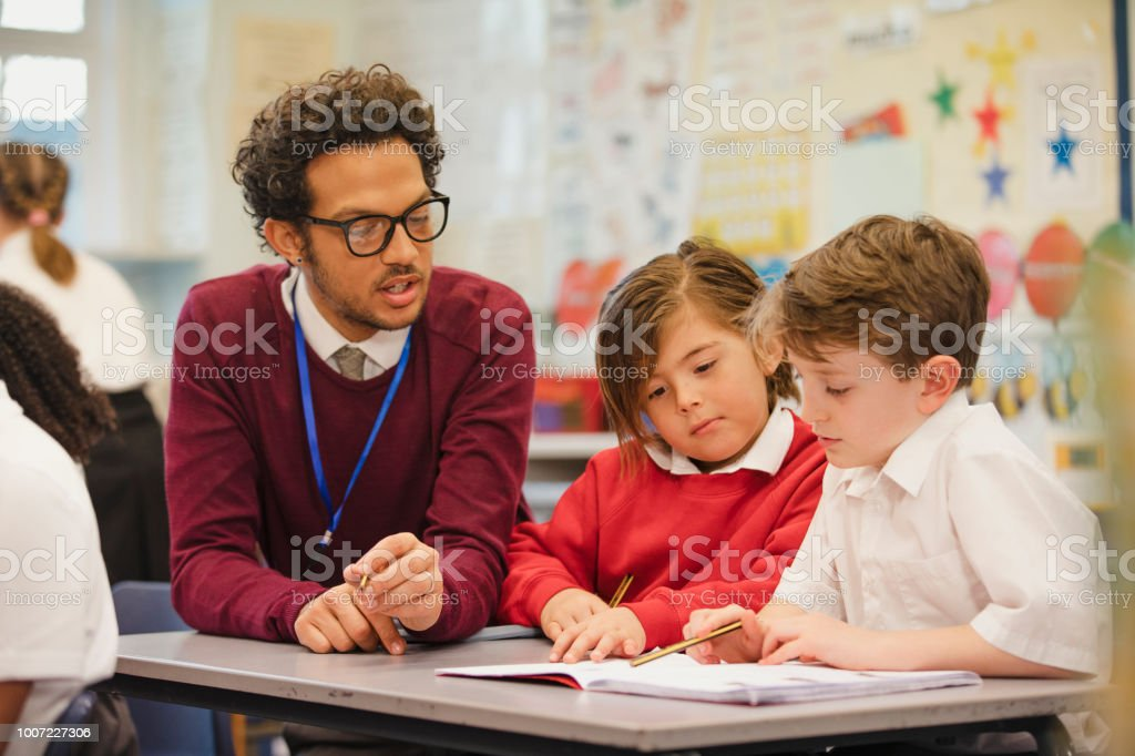 Schoolboys Work with their Teacher in Elementary Class stock photo