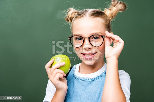 1016623732istockphoto schoolchild holding apple and touching glasses near blackboard 1016623590