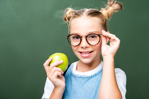 1016623732 istock photo schoolchild holding apple and touching glasses near blackboard 1016623590