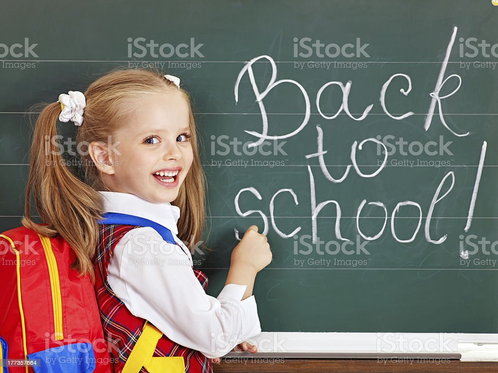 Schoolchild writting on blackboard. stock photo