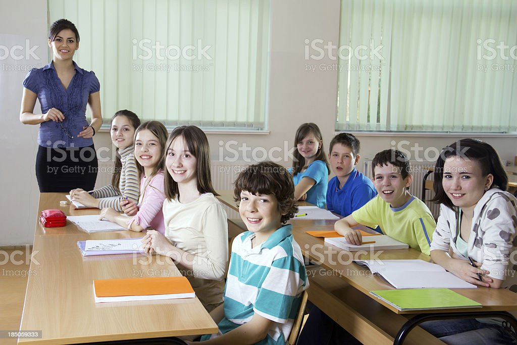 Schoolchildren and a teacher in classroom looking at camera. royalty-free stock photo