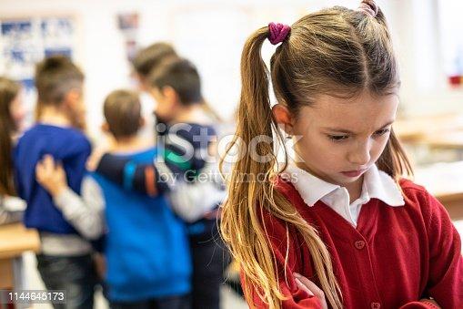 Group of schoolchildren bullying a cute girl in classroom