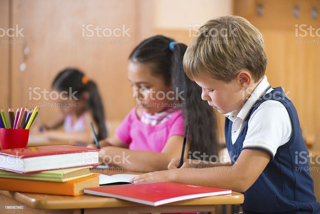 Schoolchildren during lesson in classroom at school stock photo