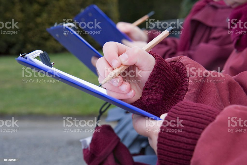 Schoolchildren filling out forms on clipboards royalty-free stock photo