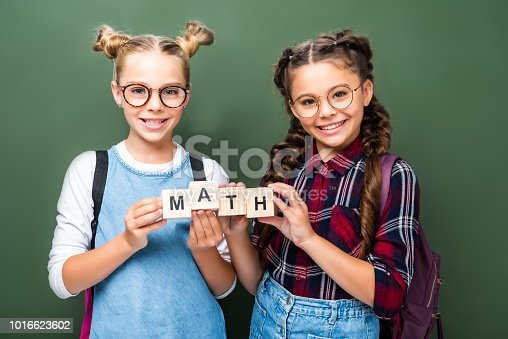 1016623732istockphoto schoolchildren holding wooden cubes with word math near blackboard 1016623602