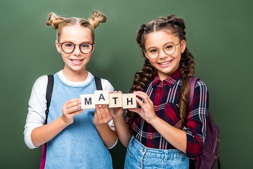 1016623732 istock photo schoolchildren holding wooden cubes with word math near blackboard 1016623602