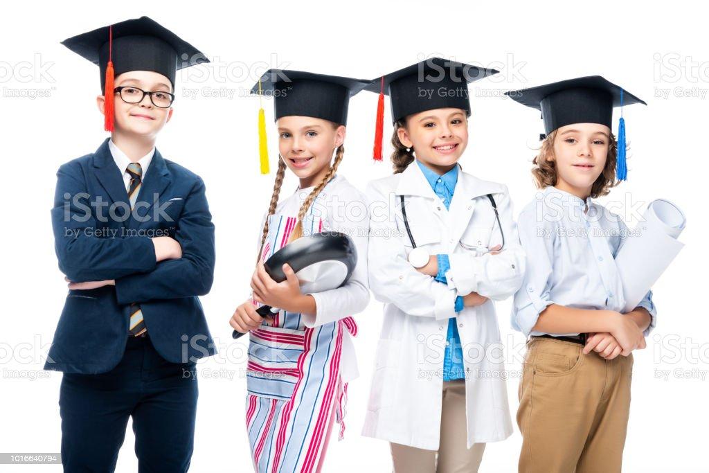 e1cf59c7a escolares en los trajes de diferentes profesiones y casquillos de la graduación  aislados en blanco foto
