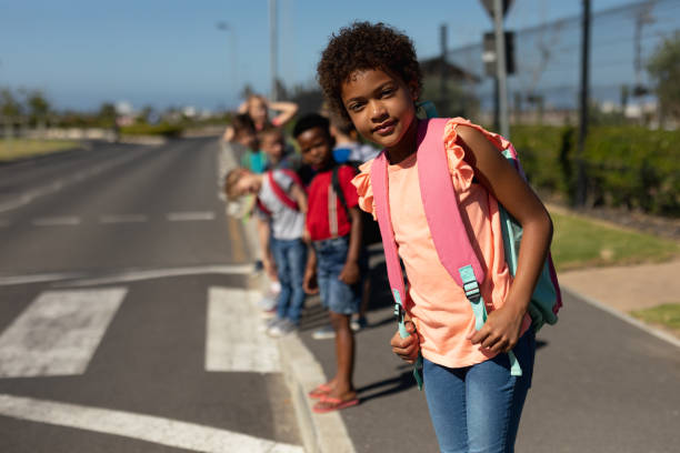 Schoolchildren looking for traffic while waiting to cross the road stock photo