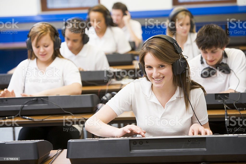 Schoolchildren practicing on keyboards in music class royalty-free stock photo