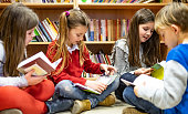 Group of children sitting on library floor and searching a books