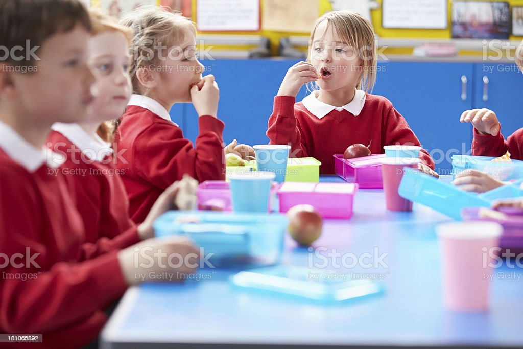 Schoolchildren sitting at table eating lunch royalty-free stock photo