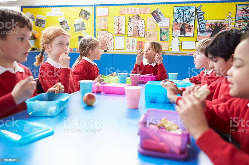 Schoolchildren Sitting At Table Eating Lunch stock photo