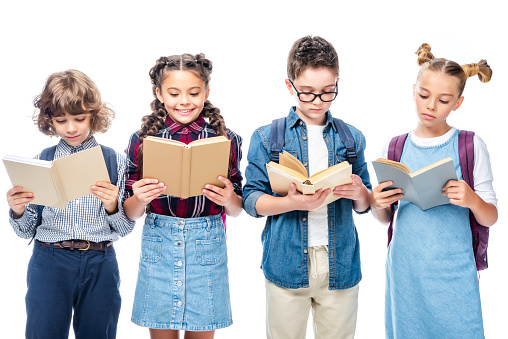 1016623732 istock photo schoolchildren standing and reading books isolated on white 1016623354