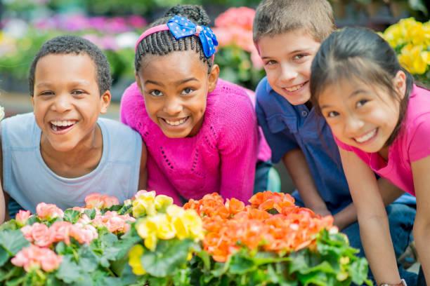 School children posing near flowers