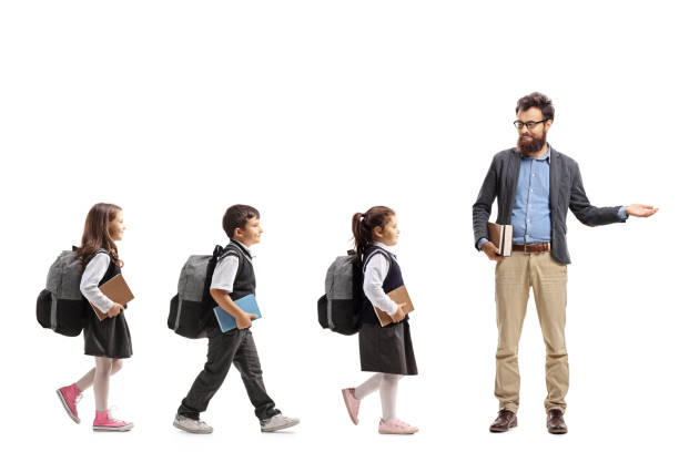 Schoolchildren walking in a line and a teacher gesturing welcome with his hand stock photo