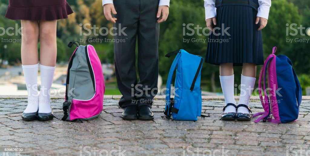 Schoolchildren with backpacks stand in the park ready to go to school, long photo royalty-free stock photo
