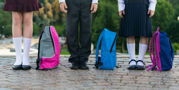Schoolchildren with backpacks stand in the park ready to go to school, long photo stock photo