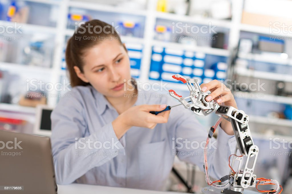schoolgirl adjusts the robot arm model stock photo