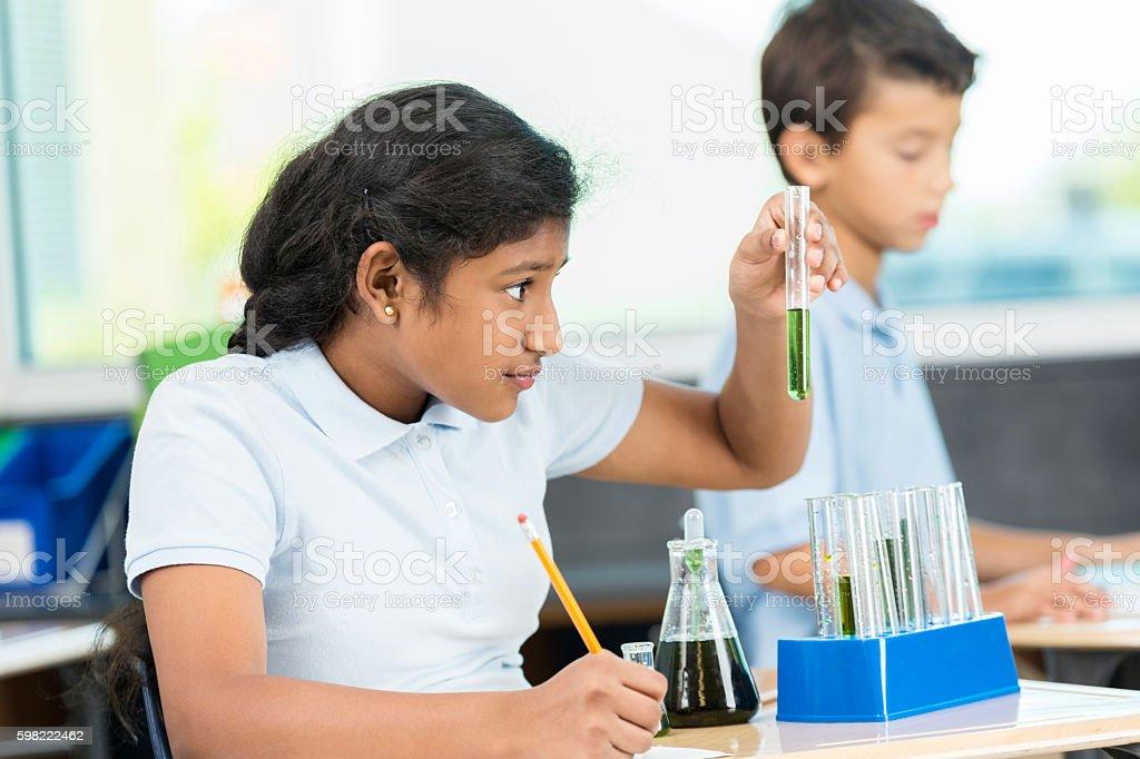Schoolgirl analyzes liquid in test tube foto royalty-free