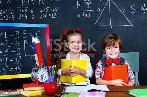 641236862 istock photo Schoolgirl and schoolboy in classroom at elementary school 1161733980