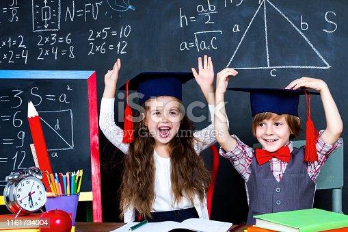 143176157 istock photo Schoolgirl and schoolboy in classroom at elementary school 1161734004