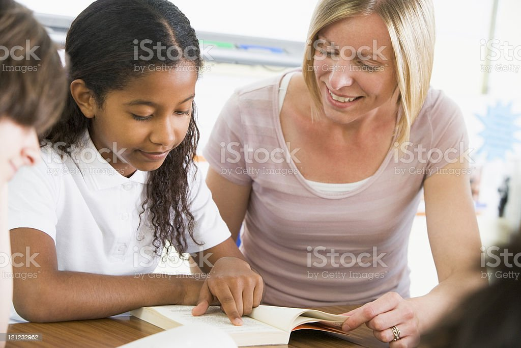 Schoolgirl and teacher reading a book in class royalty-free stock photo
