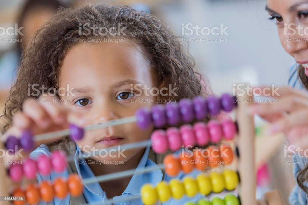 Schoolgirl concentrates while using an abacus during math class stock photo
