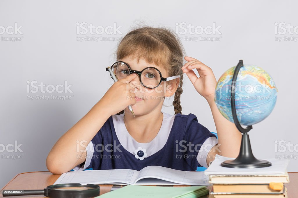 Schoolgirl corrects glasses while sitting at a desk in stock photo