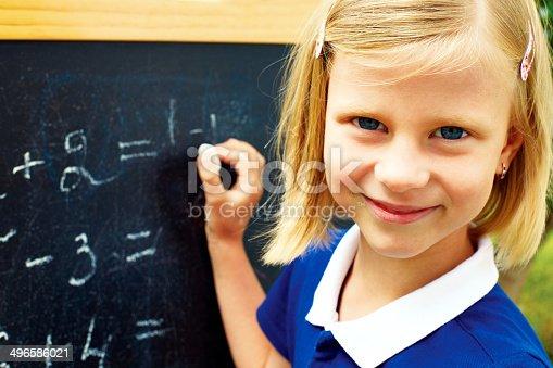 istock schoolgirl decides on a blackboard mathematical tasks 496586021