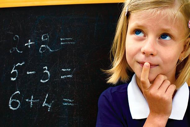 schoolgirl doing arithmetic on blackboard stock photo