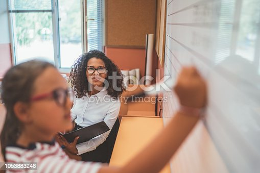 istock Schoolgirl doing math at whiteboard 1053883246