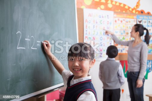 161754253istockphoto Schoolgirl doing math equation on the black board 458843799